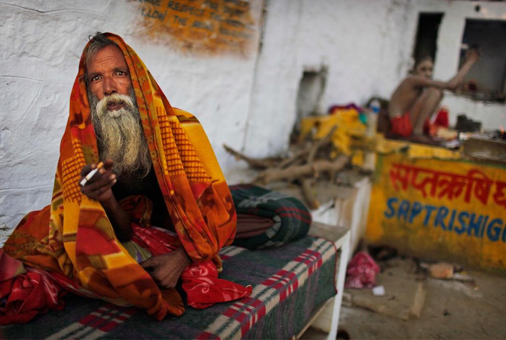 28. Индийский праведник ждет милостыню у священного озера Пушкара в Индии в пятницу 30 октября 2009 года. (AP Photo/Kevin Frayer)