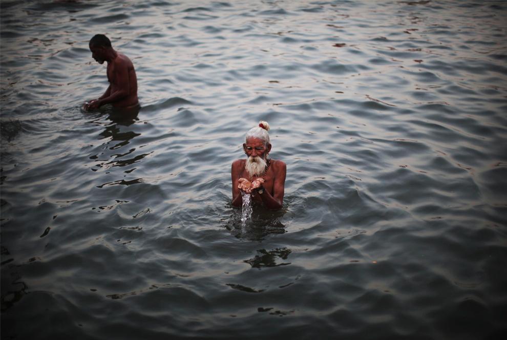 29. Индийский праведник купается на краю священного озера Пушкара в пятницу 30 октября 2009 года. Каждый день в озеро закачивается вода из баллонов, чтобы удовлетворить огромное количество паломников, приходящих сюда каждый год. (AP Photo/Kevin Frayer)