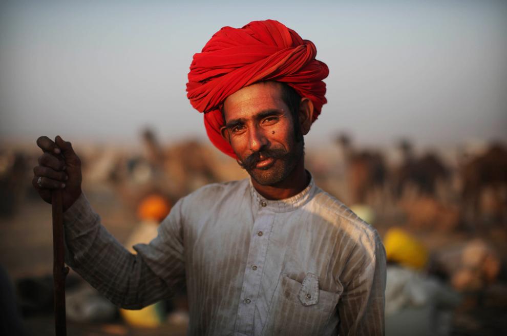 30. Погонщик верблюдов позирует для фото на рынке домашнего скота в Пушкар Мела, Раджастан, Индия, в четверг утром 29 октября 2009 года. (AP Photo/Kevin Frayer)