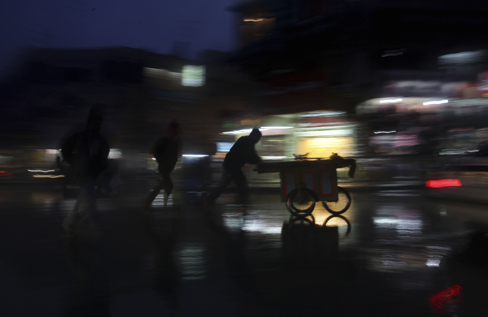 7) Палестинский торговец толкает свою тележку под проливным дождем в городе Рамалла на Западном берегу, в понедельник, 2 ноября. (AP/Muhammed Muheisen)