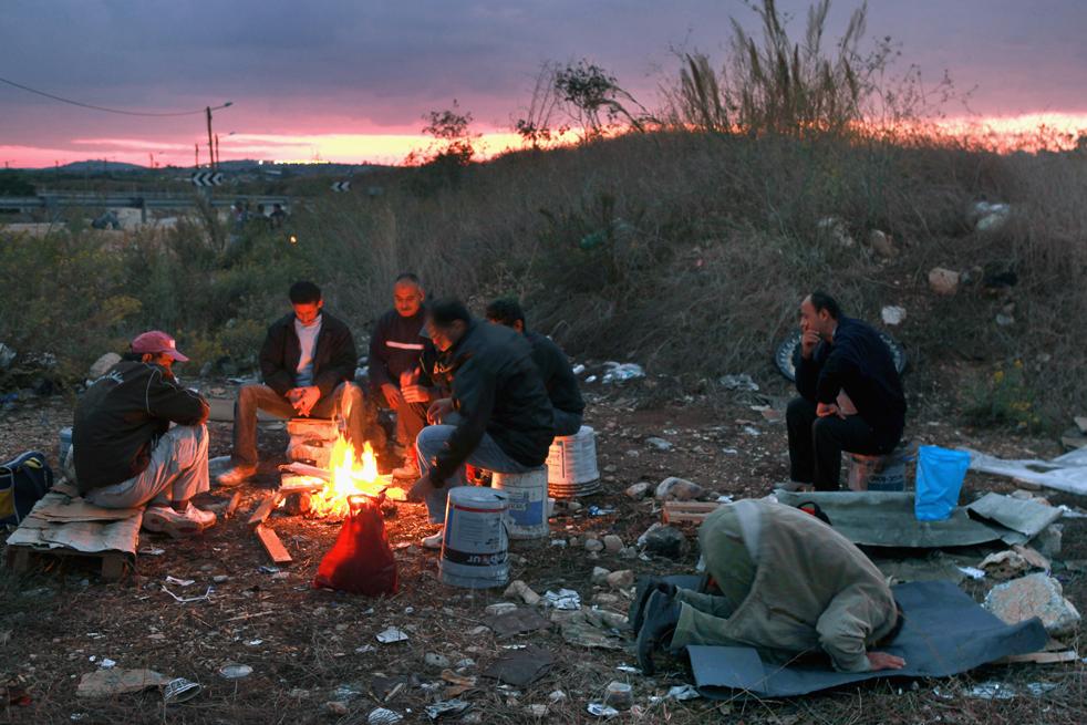 4) Палестинец во время мусульманской утренней молитвы рядом со своими товарищами, которые сидят вокруг костра в ожидании своих израильских работодателей. Снимок сделан 1 ноября, на пересечении с Эяль на Западном берегу центральной части Израиля. (Getty Images/David Silverman)