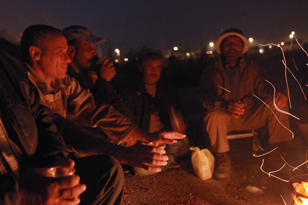 3) Палестинские рабочие день греются у костра в ожидании своих израильских работодателей. В тот день, 1 ноября, резко упала температура в преддверии зимы. Снимок сделан на пересечении Эяль с Западного берега, в центральной части Израиля. (Getty Images/David Silverman)