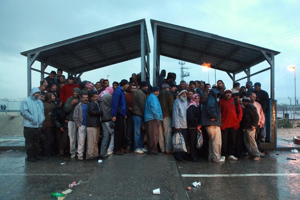 2) Палестинские рабочие толпятся под укрытием от дождя 3 ноября, на пересечении Эяль в центральной части Израиля. (Getty Images/David Silverman)