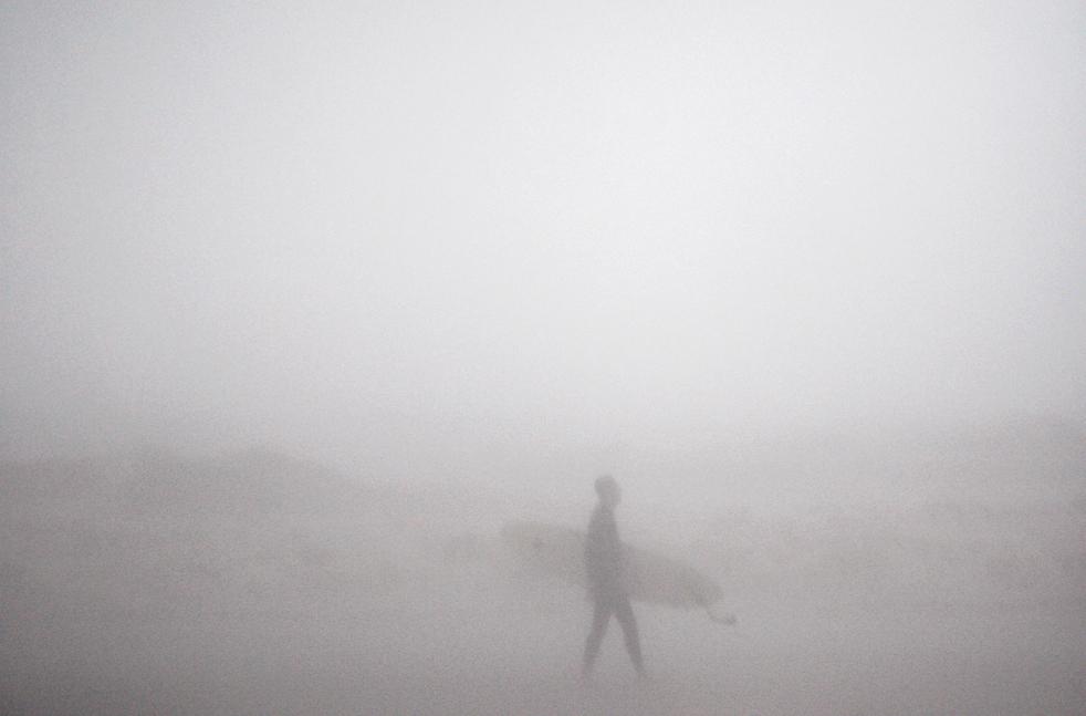 10)  Серфер идет под дождем и порывами ветра, который бушует над Средиземным морем, на пляже в Герцлии, недалеко от Тель-Авива, Израиль, в понедельник, 2 ноября. (AP/Ariel Schalit)
