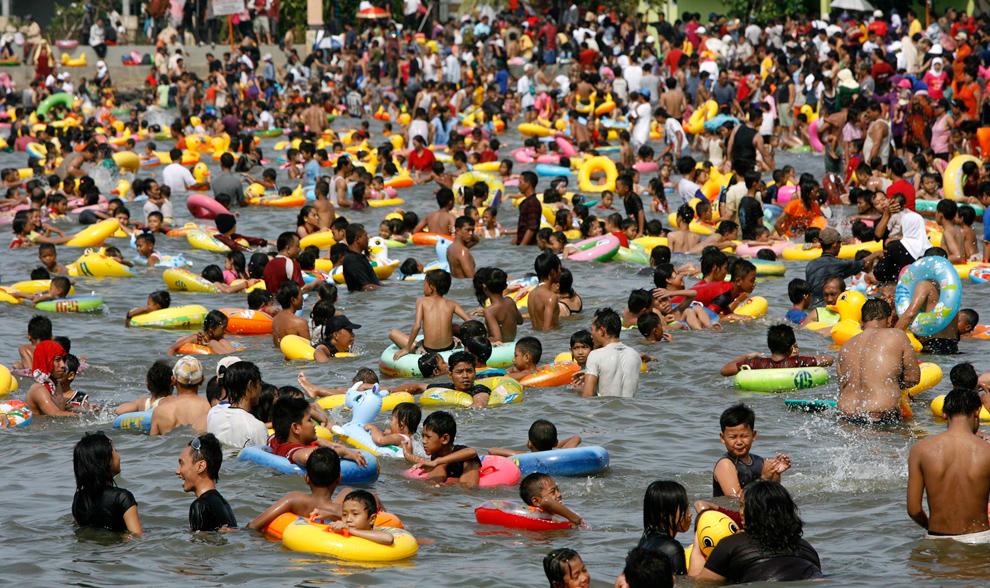 5. Индонезийцы играют в воде на пляже Анкол на празднике Эйд аль-Фитр в Джакарте, Индонезия, 21 сентября 2009 года. (REUTERS/Crack Palinggi)