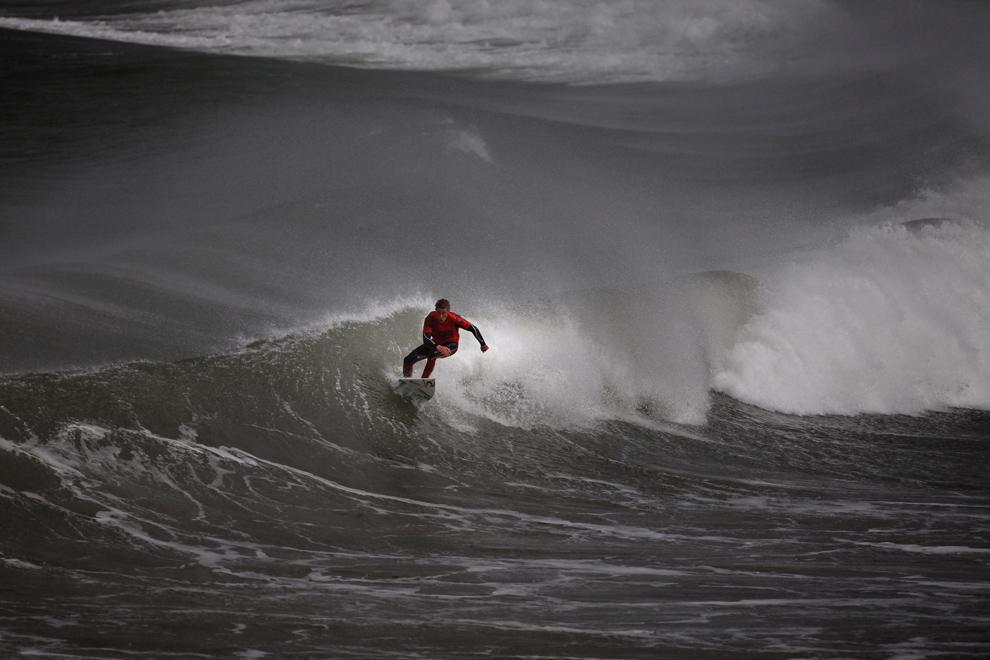 15. Серфер сражается с ветром и волнами на чемпионате «UK Pro Surfing Tour» 14 ноября 2009 года в Ньюквей, Англия. Это последнее мероприятие среди серфингистов-профессионалов  Великобритании в этом году. Оно должно было проводиться на главном пляже Фистрал, но плохие погодные условия вынудили организаторов переехать в более закрытый залив в Ньюквей. (Matt Cardy/Getty Images)