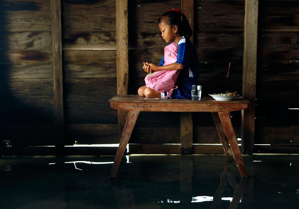 17. Ани Триастути молится на столе в затопленном доме в поселке Мондолико в Демаке, провинция Центральная Ява, 14 ноября 2009 года. По словам жителя деревни Сунарти Триастути, этот поселок, находящийся в одном километре от моря и с населением всего в 188 семей, затапливается раз в три года из-за поднимающегося уровня моря. Триастути также говорит, что наводнения уничтожили поля, и жителям деревни приходится ездить в город, чтобы найти средства к существованию. (REUTERS/Beawiharta)