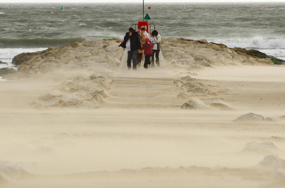 18. Семья закрывается от песчаной бури на пляже в Сэндбэнкс недалеко от Пула, южная Англия, где из-за урагана поднялись сильные волны 14 ноября 2009 года. (AP Photo/Chris Ison/PA Wire)