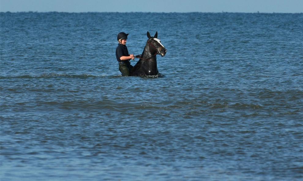 22. Член Королевской артиллерии Великобритании охлаждает себя и своего коня после галопа по пляжу во время ежегодного отдыха на курорте Блэкпул 16 сентября 2009 года. (Christopher Furlong/Getty Images)