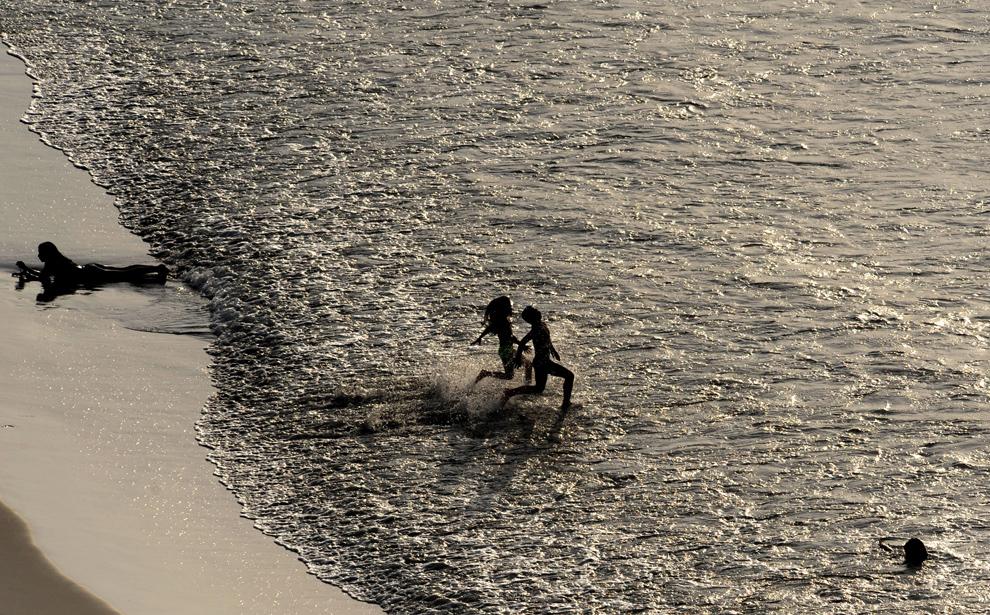 26. Колумбийцы бегут в воду на пляже в Картагене, Колумбия, 14 ноября 2009 года. (RODRIGO ARANGUA/AFP/Getty Images)