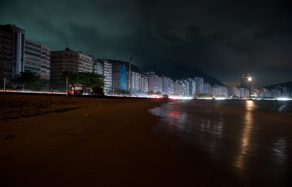 30. Пляж Копакабана, освещаемый лишь фарами и аварийными огнями, во время отключения электричества в Рио де Жанейро 10 ноября 2009 года. Крупная авария на электростанции повергла крупнейшие города Бразилии и миллионы жителей в темноту во вторник ночью. (AP Photo/Felipe Dana)