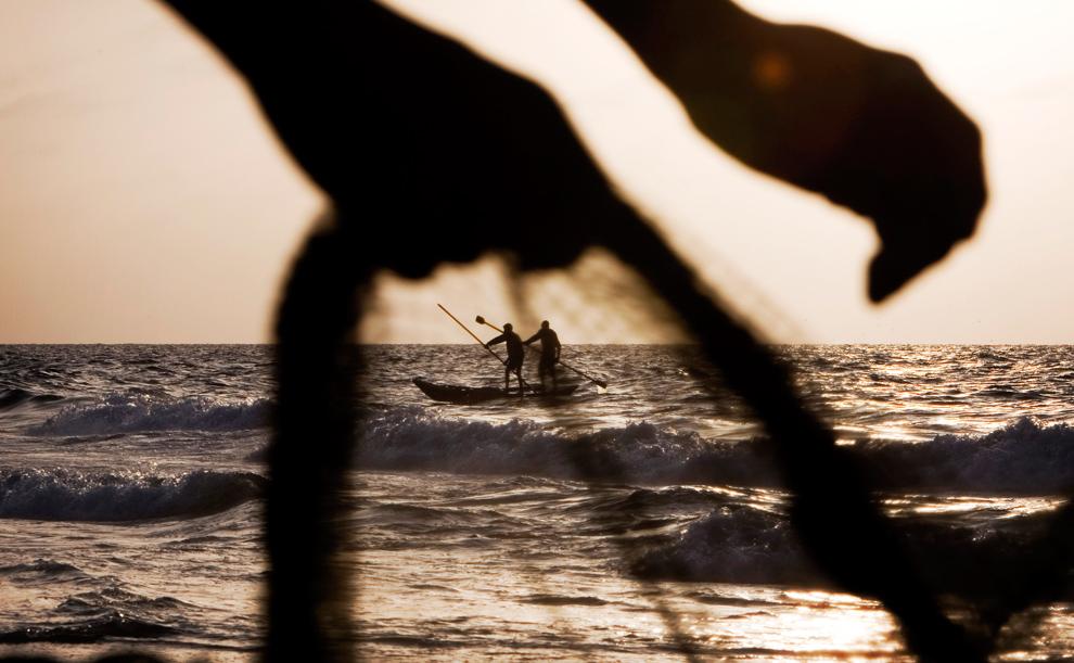 31. Палестинский рыбак достает сеть на пляже в Газе на закате 9 ноября 2009 года. (AP Photo/Tara Todras-Whitehill)