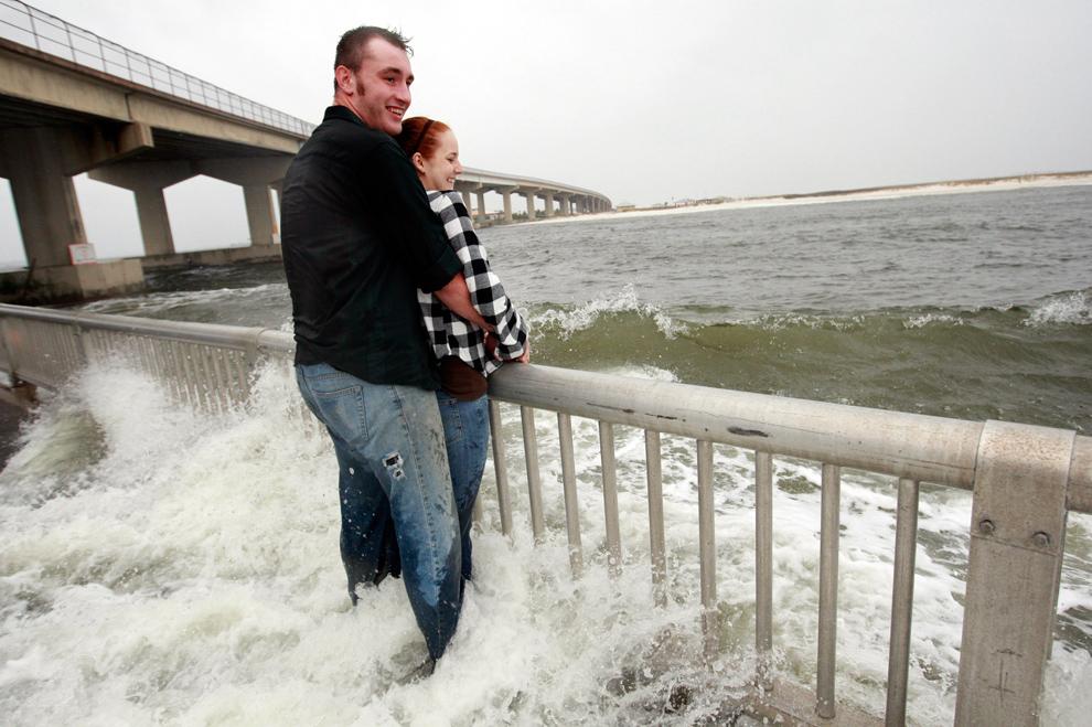 32. Джейсон Роджерс и его девушка Линдси Браун наблюдают, как дождь и ветер от тропического урагана Ида приближается к побережью у Пердидо Пасс в Галф Шорс, штат Алабама, 9 ноября 2009 года. (AP Photo/Dave Martin)