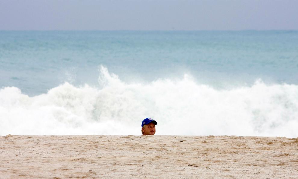 36. Мужчина идет по пляжу в Канкуне, пока ураган Ида проходит мимо в нескольких километрах от берега 8 ноября 2009 года. За последние несколько лет ураганы поглотили большую часть известных пляжей Канкуна. (REUTERS/Victor Ruiz)