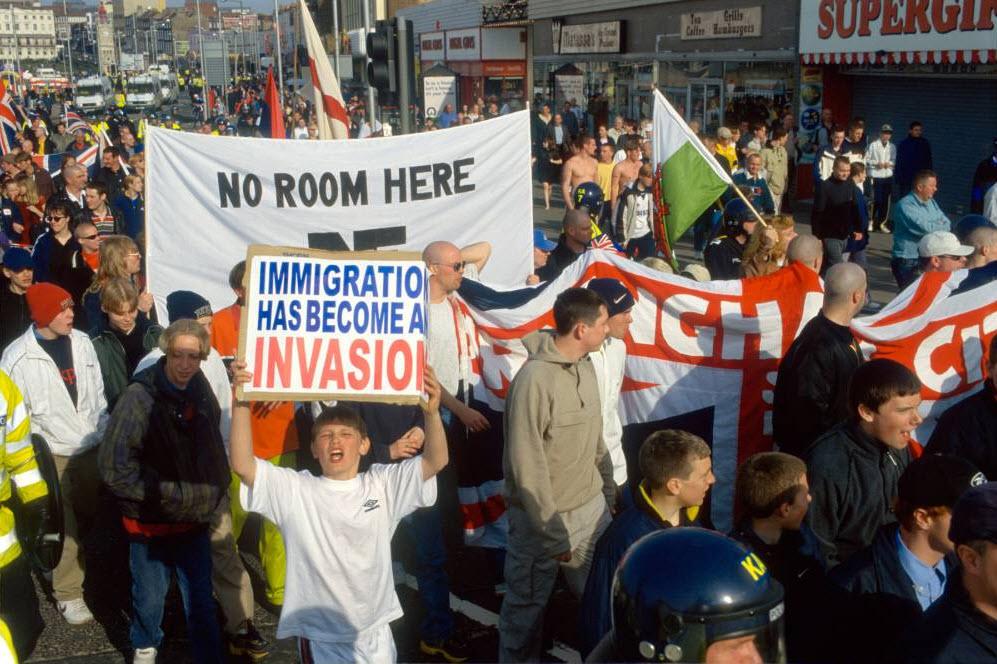 4. Женщина, чей балкон выходит на маршрут марша «Любите музыку, ненавидьте расизм», проходящем через Бетнал Грин к парку Виктория, вывесила флаги в поддержку расистской Британской Националистической партии в Лондоне 27 апреля 2008 года. (David Hoffman)