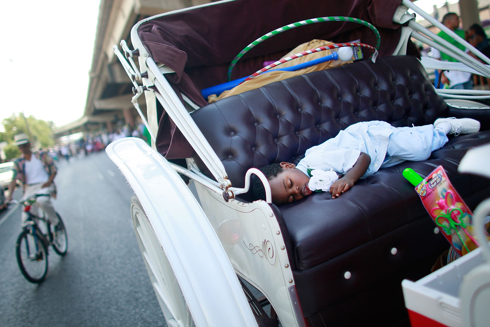 9. Мальчик спит во время традиционного парада «Original Big 7 Social and Pleasure Club» в Новом Орлеане. Эта традиция возникла, когда афро-американцы начали организовывать парады с оркестрами, устраивая «похороны в стиле джаз» для своих товарищей. (Getty Images / Mario Tama)