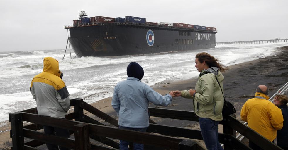 1. Люди смотрят на баржу, которую оторвало от буксира и прибило к берегу в районе Сэндбридж города Вирджиния Бич, штат Вирджиния, в пятницу 13 ноября во время тропического урагана Ида. (AP / Steve Helber)