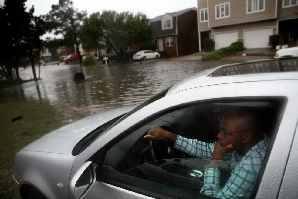 3. Деррик Роймель ждет в машине на возвышенности, пока вода уйдет с улицы Шор Драйв утром 13 ноября в городе Вирджиния Бич, штат Вирджиния. (The Virginian-Pilot / Vicki Cronis-Nohe)