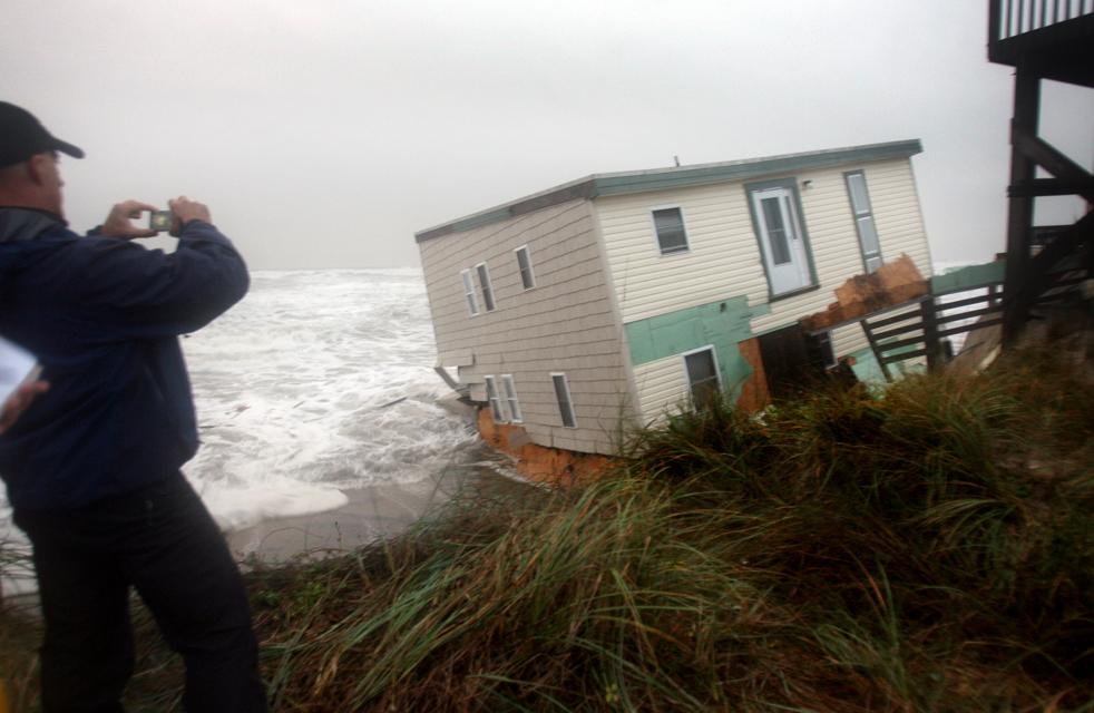 7. Ведущий прогноза погоды Джим Кантор фотографирует дом, обрушившийся в океан, в Саут Нагс Хэд, штат Северная Каролина, 12 ноября. (The Virginian-Pilot / Steve Earley)