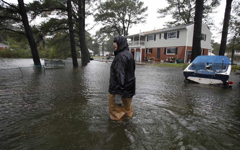 9. Доктор Г. Маркс Ричард идет к своему дому по заднему двору, затопленному тропическим ураганом Ида, в Норфолке, штат Вирджиния, 12 ноября. (AP / Steve Helber)