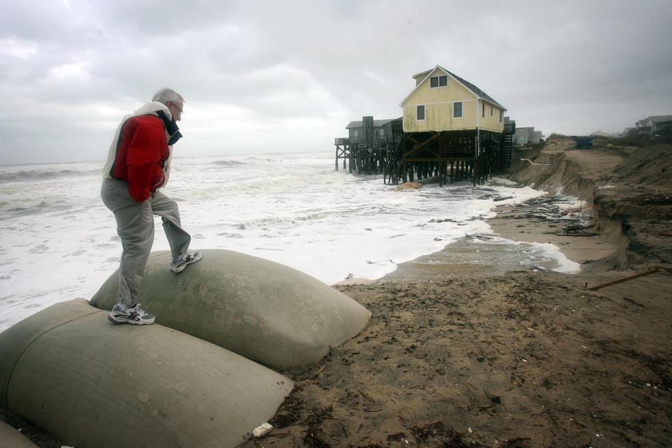11. Майкл Грэм из Саванны, штат Джорджия, смотрит на размытый утренним приливом берег в Саут Нагс Хэд, штат Северная Каролина, 12 ноября. (The Virginian-Pilot / Steve Earley)