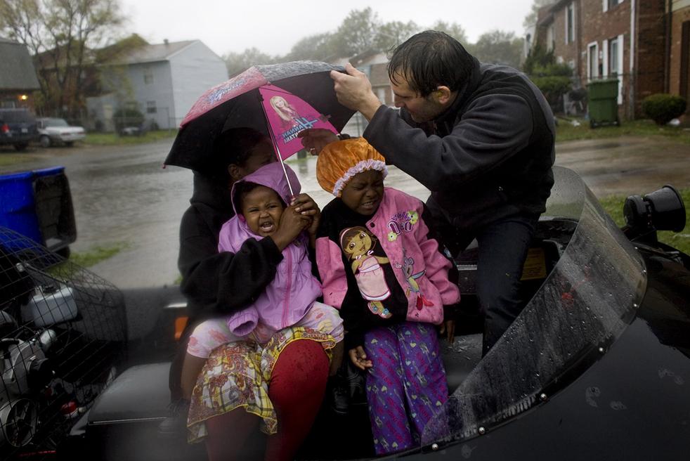 12. Тэд Агоглия из службы неотложной помощи, которая базируется в Ноксвилле, штат Теннеси, эвакуирует семью Бейкер из Спартан Вилладж 12 ноября, так как через несколько часов здесь ожидается наводнение. Канал CNN назвал Агоглия одним из 10 героев года. (The Virginian-Pilot / Stephen M. Katz)