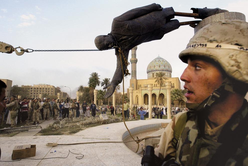 1. Иракские граждане и солдаты армии США сносят статую Саддама Хусейна в центре Багдада 9 апреля 2003 года. (AP Photo/Jerome Delay, File)