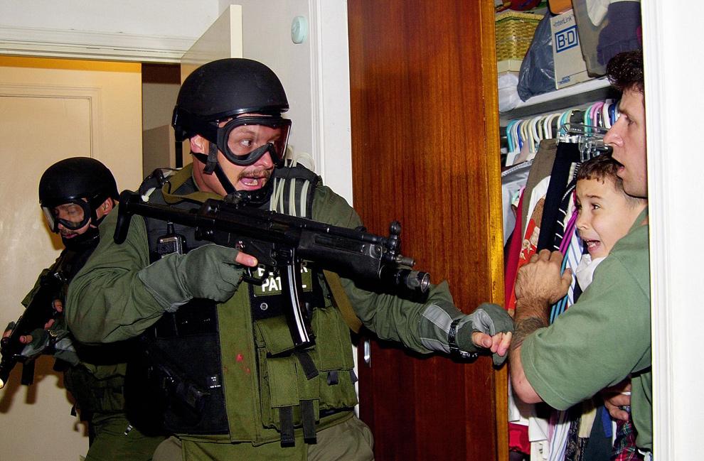 2. Шестилетний Элиан Гонзалез кричит на руках у Донато Далримпла – человека, который спас его в море в ноябре 1999 года – в то время, как федеральные агенты пытаются забрать мальчика в доме его родственника в Майами 22 апреля 2000 года. Верховный суд США постановил 28 июня 2000 года, что отказывается выдать мальчика, собираясь отправить его обратно на Кубу 28 июня. (AL DIAZ/AFP/Getty Images)