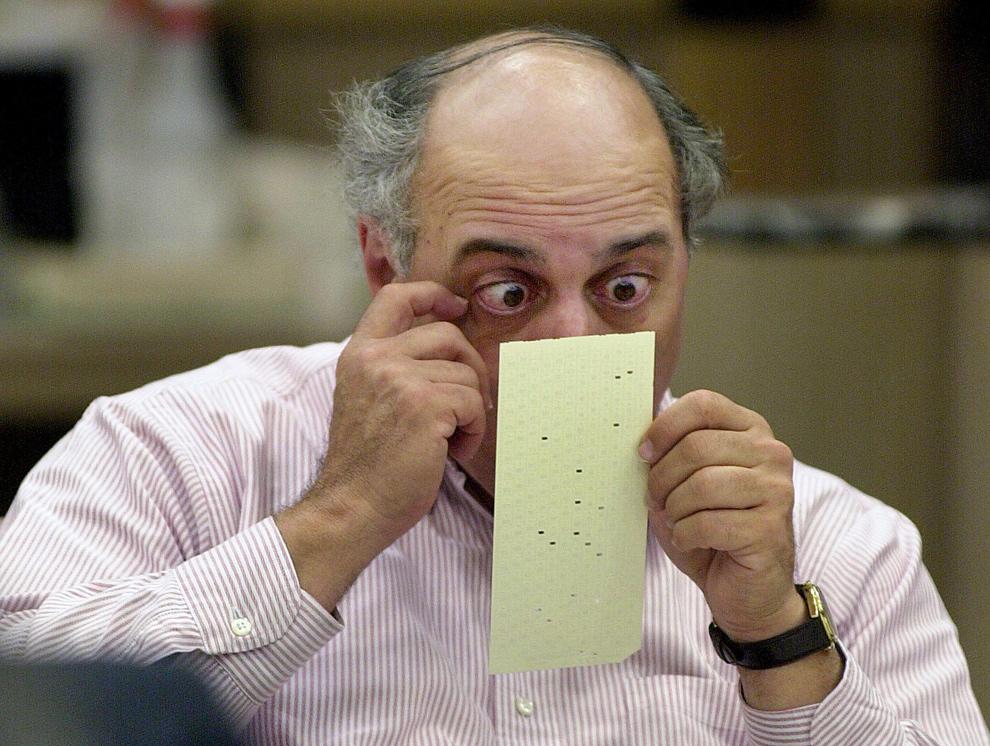 4. Член избирательной комиссии Бровард Каунти Роберт Розенберг смотрит на сомнительный бюллетень 25 ноября 2000 года в здании суда Бровард Каунта в Форт Лодердейл, штат Флорида. Избирательная комиссия Бровард Каунти продолжает ручной пересчет голосов, чтобы успеть к 26 ноября, как того потребовал Верховный суд штата Флорида, чтобы принять бюллетени к сертификации. (RHONA WISE/AFP/Getty Images)