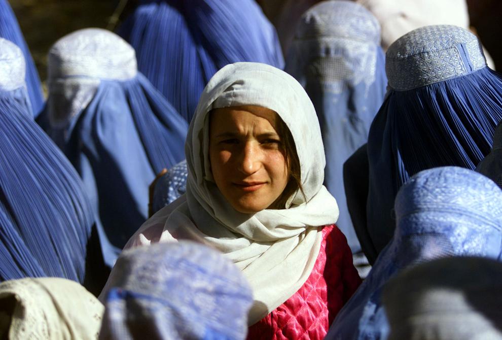 8. Афганская девушка показывает свое лицо впервые после пяти лет правления талибов, ожидая еду у центра раздачи в Кабуле 14 ноября 2001 года. Прикрываясь Исламом, талибы приказали всем женщинам носить паранджу, скрывающую их с ног до головы. (REUTERS/Yannis Behrakis)