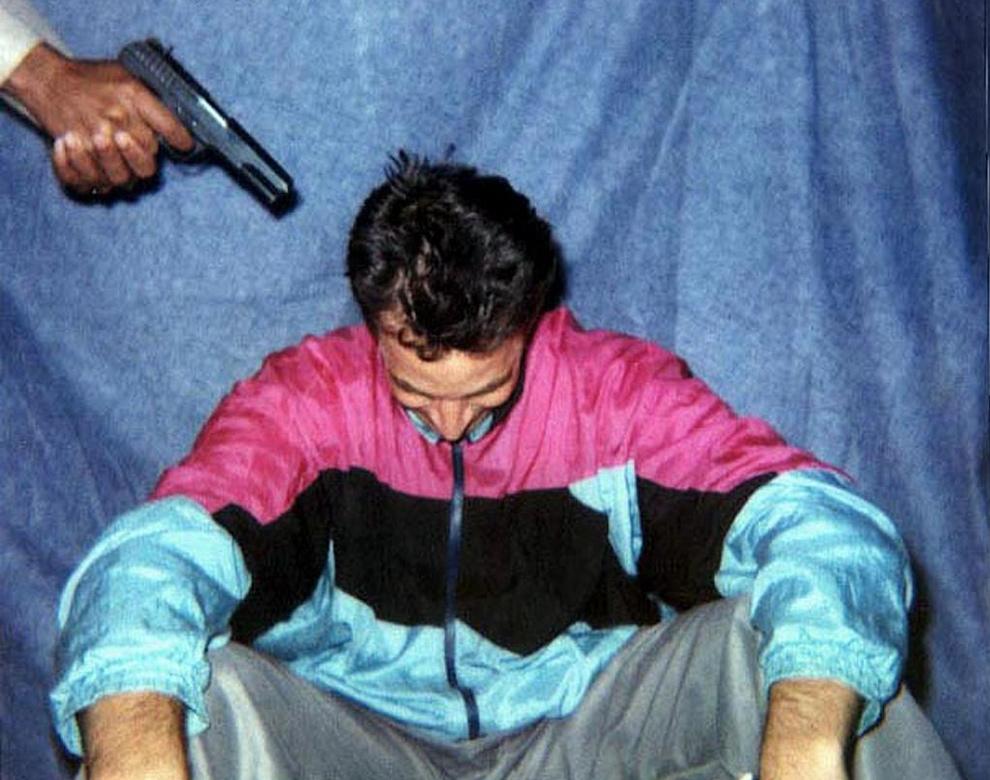 9. На этом фото, полученном 30 января 2002 года, вы видите репортера издания «Wall Street Journal» Дэниела Перла в неизвестном месте с пистолетом у головы. Позднее похитители обезглавили репортера, разрезали его тело на куски и сожгли у границ Карачи. (AFP/Getty Images)
