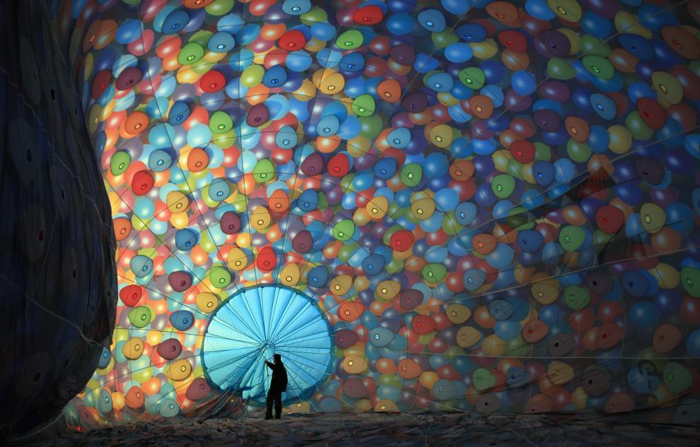 1) Мужчина проверяет веревки внутри воздушного шара во время подготовки к самому большому в Европе фестивалю воздушных шаров. (Matt Cardy/Getty Images News/ fotobank.ua / 7 августа 2009/ Англия, Бристоль)