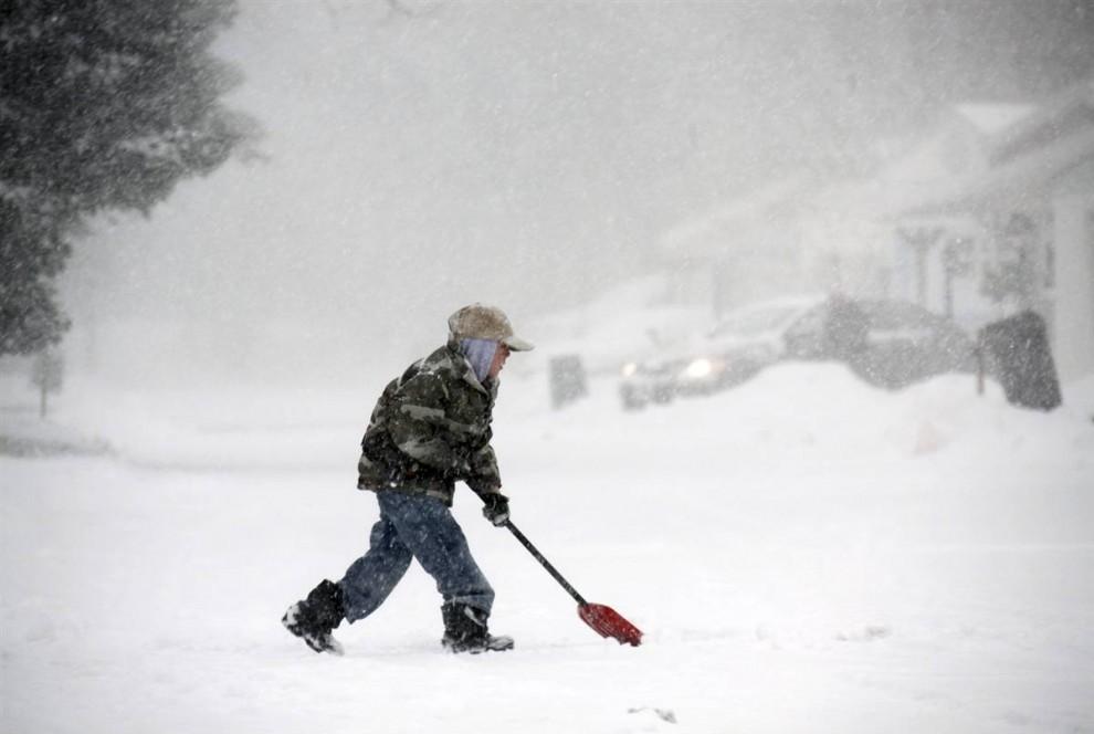 9-летний Алекс Брюх убирает лопатой снег на подъезде к своему дому в Клэренсе, пригороде Буффало, штат Нью-Йорк, 10 декабря. (David Duprey / AP)