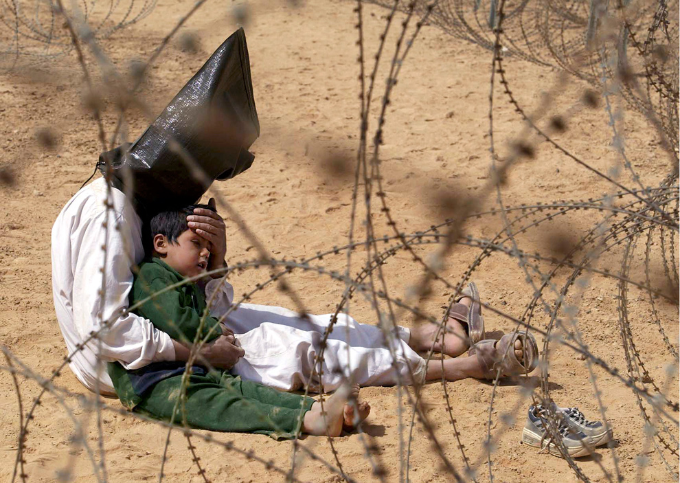 12. Иракский военнопленный успокаивает своего четырехлетнего сына в центре перегруппировки военнопленных 101-ой воздушно-десантной дивизии недалеко от Ан Наджаф, Ирак, 31 марта 2003 года. Мужчину схватили в Ан Наджафе вместе с сыном, и американские военные решили не разлучать их. (AP Photo/Jean-Marc Bouju, File)
