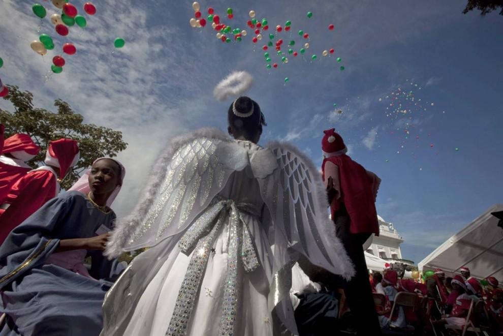 1. Дети в карнавальных костюмах участвуют в рождественском конкурсе у президентского дворца накануне Рождества в Порт-о-Пренс, Гаити.(Ramon Espinosa/AP)