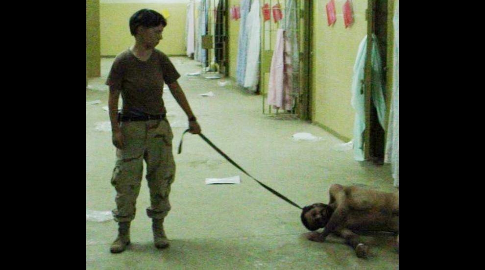 13. На этом архивном фото рядовой первого класса Линнди Ингланд держит веревку, привязанную к шее задержанного. Снимок сделан в конце 2003 года в тюрьме Абу-Грейб в Багдаде. (AP Photo, File)