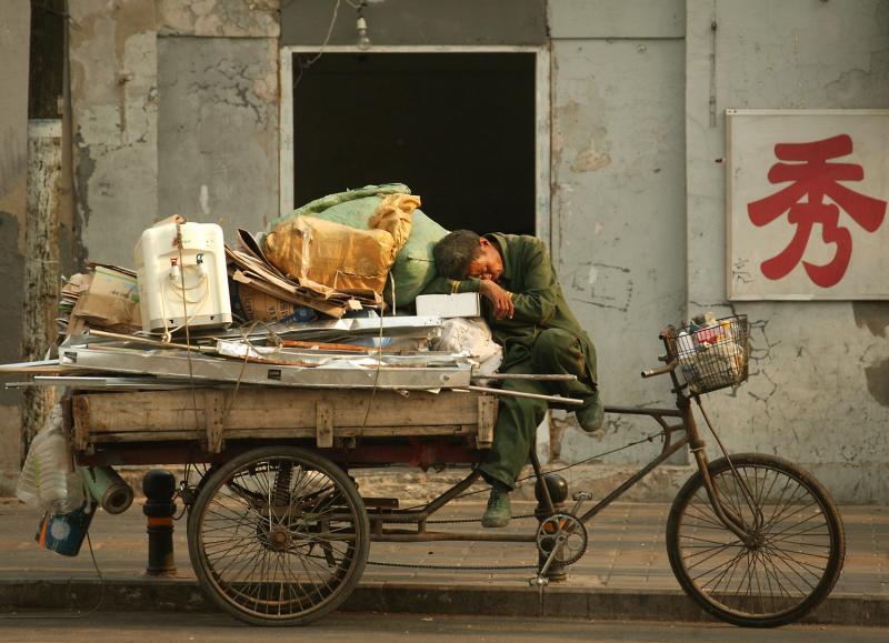 1) Китайский мигрант, собиравший мусор чтобы сдать его в утиль, решил вздремнуть на своем трехколесном велосипеде в Пекине 14 мая 2009 года. (UPI Photo/Stephen Shaver)