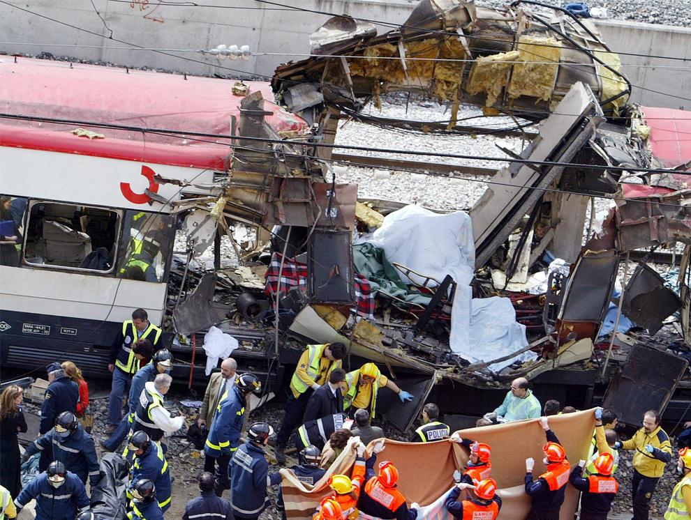 18. Тела жертв выносят после взрыва поезда недалекот от станции Аточа в Мадриде 11 марта 2004 года. По меньшей мере, 131 человек погиб и около 400 получили ранения 11 марта 2004 года в практически одновременных взрывах в трех мадридских поездах. Это был преднамеренный теракт, проведенный всего за 72 часа до всеобщих выборов в Испании. Взрывы произошли в высокоскоростном поезде дальнего следования и в двух пригородных поездах. (CHRISTOPHE SIMON/AFP/Getty Images)