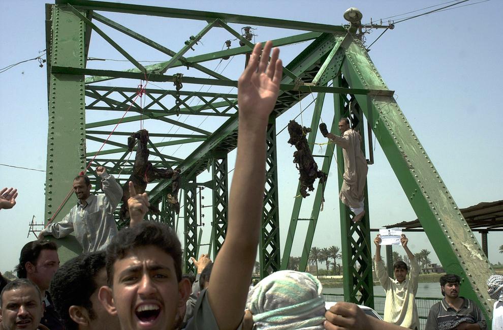 19. Иракцы выкрикивают анти-американские слоганы с висящими на заднем плане обугленными телами на мосту над рекой Евфрат в Фаллудже к западу от Багдада 31 марта 2004 года. (AP Photo/Khalid Mohammed, File)