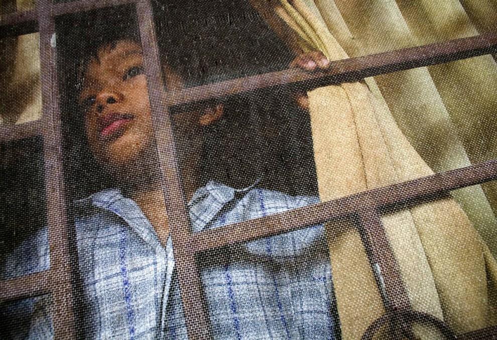 2. Мальчик смотрит в окно во время сончаса в приюте Маи Хоа в Ан Нхон Тай, Вьетнам. ВИЧ-инфицированные дети надеялись пойти в местную школу, но родители других детей высказались против из-за опасения заражения. (Justin Mott / Redux Pictures)
