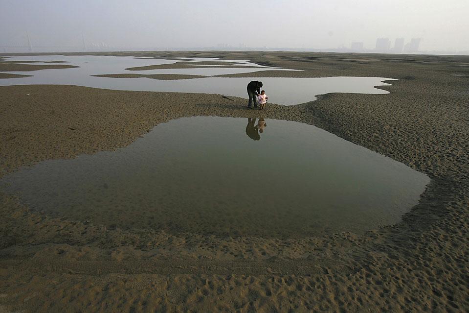 2) Местные жители идут по частично высохшему руслу реки Янцзы в Ухане, Китай. (Stringer/Reuters)