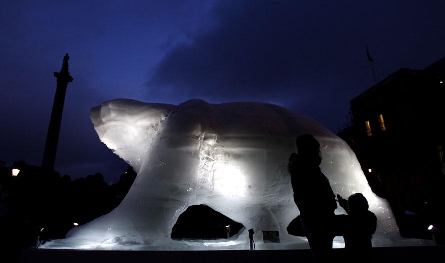 2. Уже начавшая таять скульптура белого медведя из льда в натуральную величину в сумерках на Трафальгарской площади в Лондоне. Скульптура символизирует положение белых медведей в Арктике, где тающие льды угрожают их существованию. Ледяной медведь будет таять в течение 10 дней. Слева колонна адмирала Нельсона.