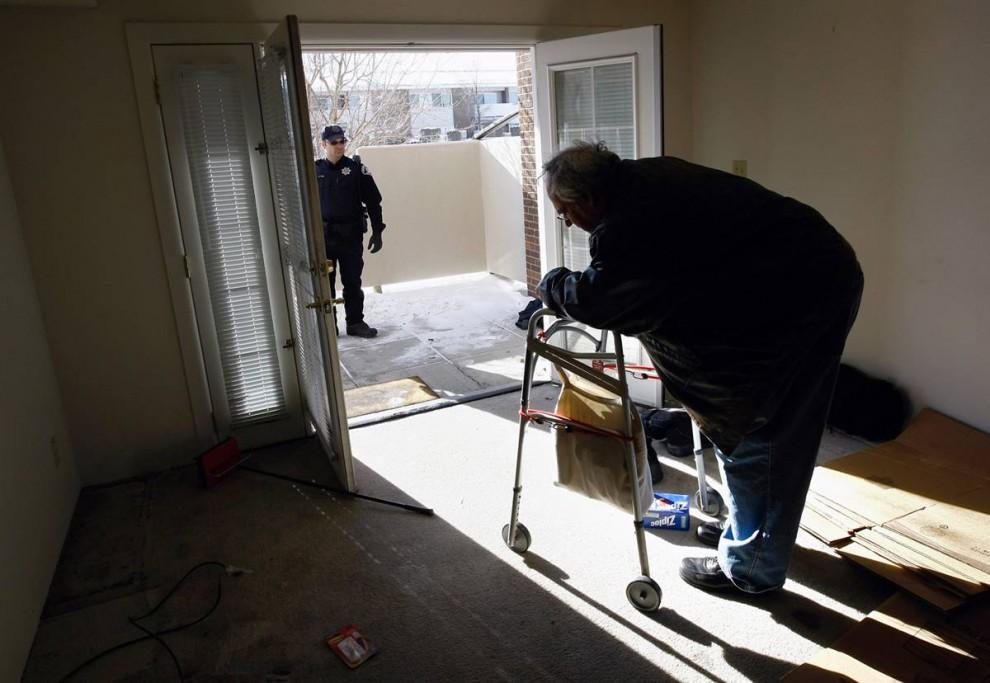 2) Заместитель шерифа Сет По ждет у входа, чтобы вывести Харви Лессера из его квартиры, после вручения бывшему жильцу постановления суда о выселении. (John Moore/Getty Images)