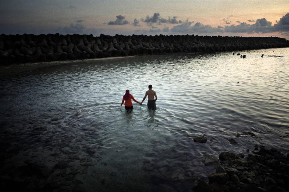 2. Мале располагается всего на 91 см выше уровня моря. К этому добавилось засыпание мелководья песком и камнями. Это приблизило остров к внешнему коралловому рифу, снижая способность рифа защищать землю от штормов и повышающегося уровня моря. Чтобы защитить Мале от штормов и приливов, вокруг государства был возведен бетонный барьер (часть его вы видите на фото) стоимостью 60 миллионов долларов. «Я выбрал Мальдивы, потому что эта страна ближе всех к уровню моря, - говорит фотограф Франческо Зизола. – Если то, что говорят ученые о глобальном потеплении правда, тогда Мальдивы будут первыми, которые уйдет под воду». (Francesco Zizola/Consequences by NOOR)
