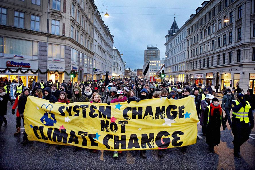 """3) Около тысячи людей прошли по улицам Копенгагена в последний день саммита ООН по вопросам изменений климата. Эти люди участвовали в демонстрации в знак протеста против ареста датской полицией трех официальных представителей группы """"За климатическую справедливость"""". (AP Photo/Polfoto, Jens Dige)"""