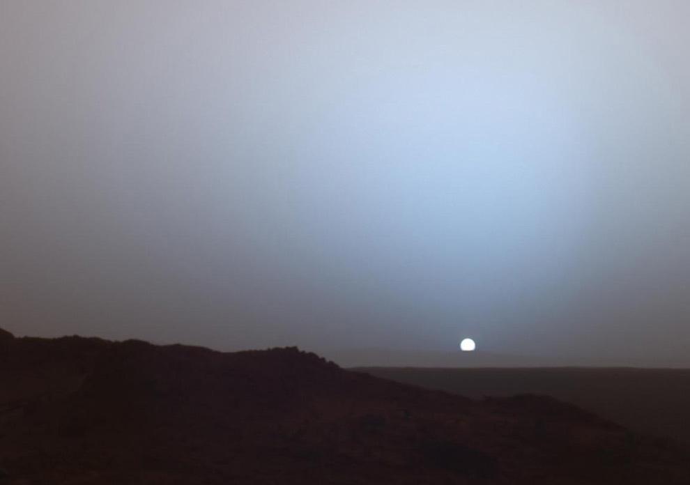 22. 19 мая 2005 года марсоход НАСА «Спирит» сделал этот удивительный снимок Солнца, заходящего за край кратера Гусева на Марсе. Эта панорамная мозаика была сделана около 18:07 марсианских суток. «Спирит» должен был бодрствовать вскоре после того, как отослал эти данные на орбитальный аппарат «Mars Odyssey» как раз перед закатом. Снимок представляет собой состав из псевдо-цветов, на котором показано небо, которое привык видеть человек, но со слегка преувеличенными цветами. (NASA/JPL/Texas A&M/Cornell)