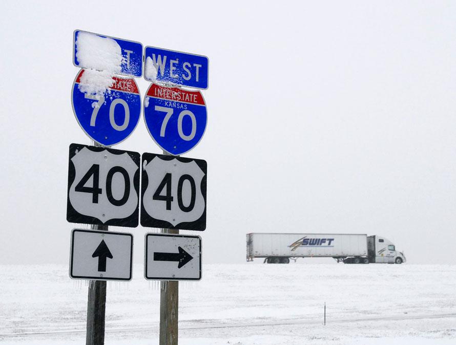 2. Снег и лед покрывают часть дорожного знака на фоне грузовика, направляющегося на запад по шоссе Interstate 70 в среду на западе от Хэйс, штат Канзас. Зимние метели пришли в Канзас, принеся с собой плохую видимость на дорогах. (AP Photo/ Hays Daily News, Steven Hausler)