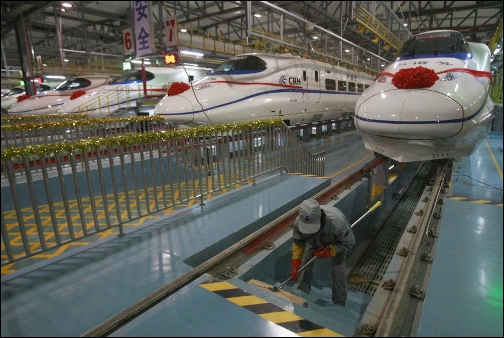 2) © REUTERS/China Daily // Рабочий депо чистит лестницу перед поездом CRH.