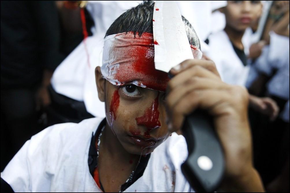 2) © Reuters / Arko Datta / / anak laki-laki memotong dirinya sendiri dengan pisau selama festival Asyura.