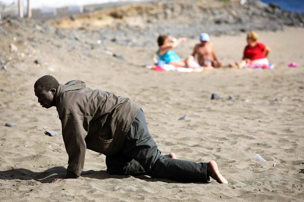 3) Иммигрант ползет мимо отдыхающих на пляже, приплыв на пляж Гран Тараджал, Канарские острова, на самодельной лодке 5 мая 2006 года. Около 38 иммигрантов приплыли на пляж на самодельном судне, и еще 39 человек были перехвачены у берегов Канарских островов при попытке добраться до европейской земли из Африки. (REUTERS/Juan Medina)